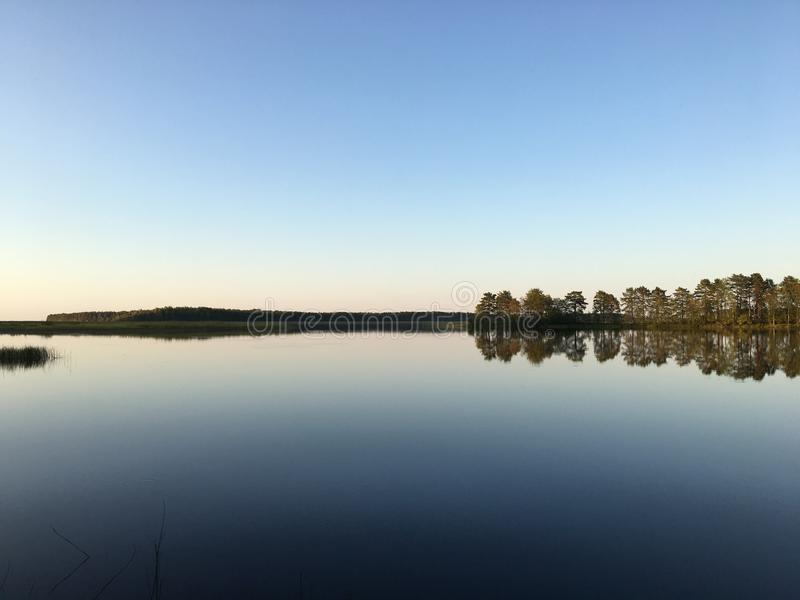 Perfect reflections on the lake in summer evening with warm colors. A unique image of the surrounding nature royalty free stock image