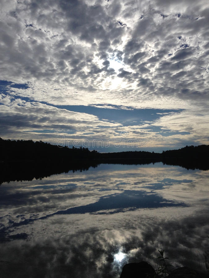 Perfect Reflections, Moon River, Muskoka, Ontario, Canada. Amazing cloud patterns are perfectly reflected in the mirror-like surface of the Moon River, Near Bala royalty free stock image