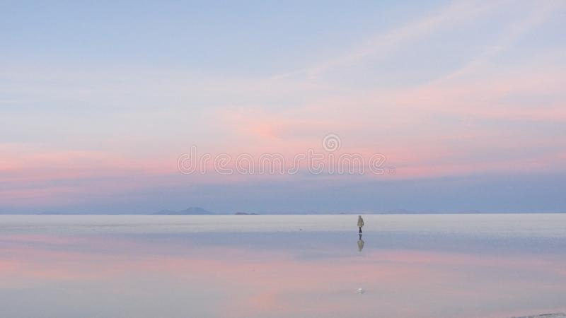 A boy walking during the sunrise, in Salar de Uyuni, Bolivia stock images