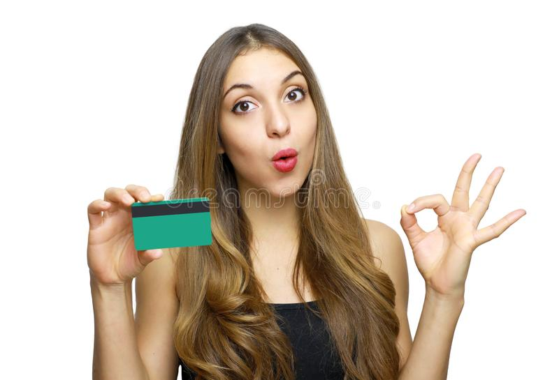 Perfect, that`s Ok! Satisfied young woman in black dress holding bank card and showing OK sign isolated on a white background royalty free stock photo