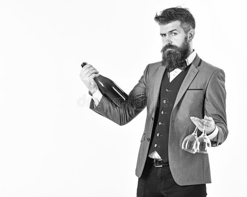 Perfect service, good manners, alcohol concept. Waiter with elegant suit, bow tie and handsome face. Mature man holds. Wineglasses and bottle of wine. Bearded royalty free stock photos
