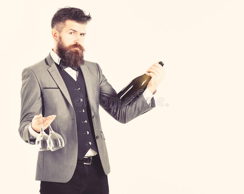 Perfect service, good manners, alcohol concept. Waiter with elegant suit, bow tie and handsome face. Mature man holds. Wineglasses and bottle of wine. Bearded stock photos