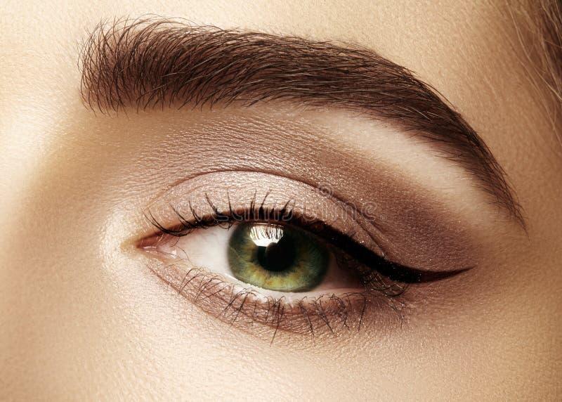 Perfect shape of eyebrows, brown eyeshadows and long eyelashes. Closeup macro shot of fashion smoky eyes visage. Beautiful macro shot of female eye with classic stock photography