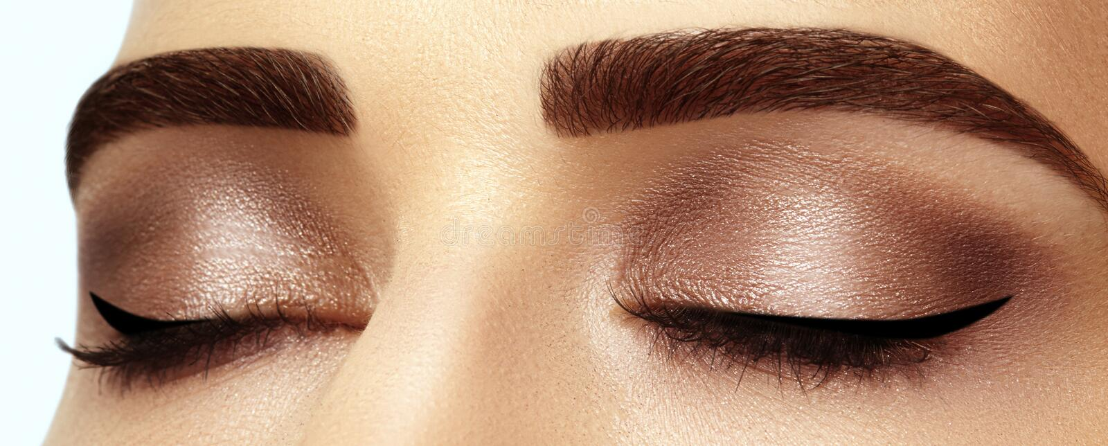 Perfect shape of eyebrows, brown eyeshadows and long eyelashes. Closeup macro shot of fashion smoky eyes visage stock photography