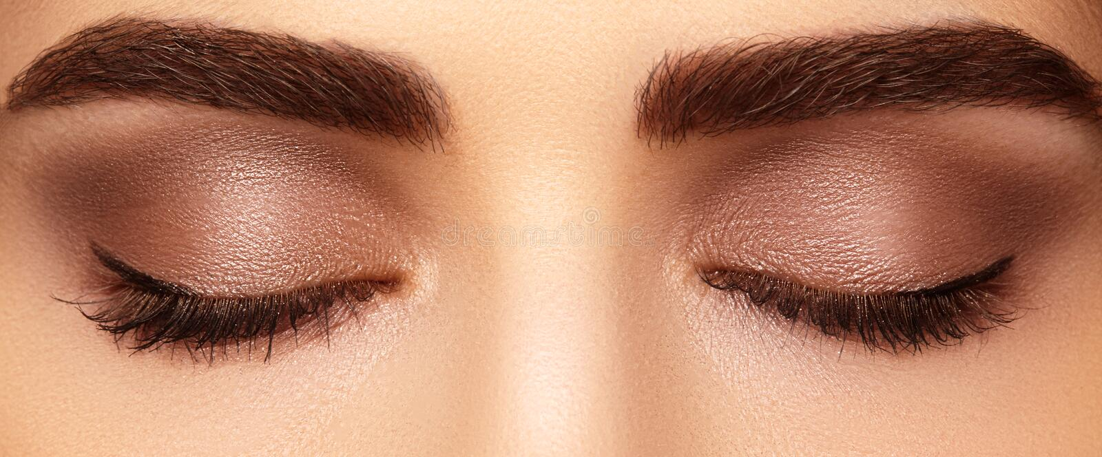 Perfect shape of eyebrows and extremly long eyelashes. Macro shot of fashion eyes visage. Before and after. Beautiful macro shot of female eye with classic smoky stock images