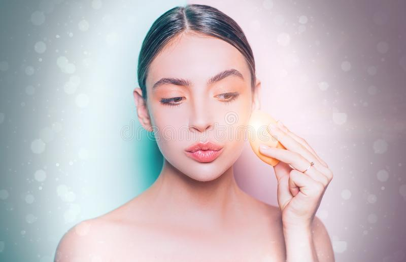 Perfect skin tone. Apply concealer and cosmetic highlighter. Girl hold cosmetic applicator. Woman spreading cream on her. Face. Skin cream concept. Facial care royalty free stock images