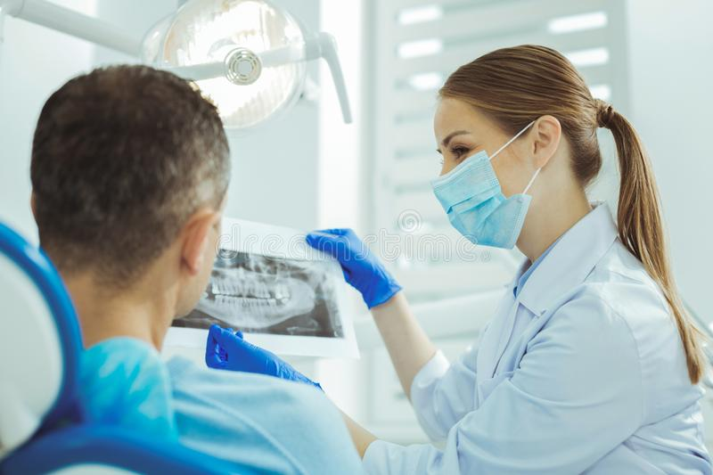 Positive delighted dentist consulting her visitor. Perfect smile. Cheerful professional doctor sitting in semi position while examining roentgenogram stock image