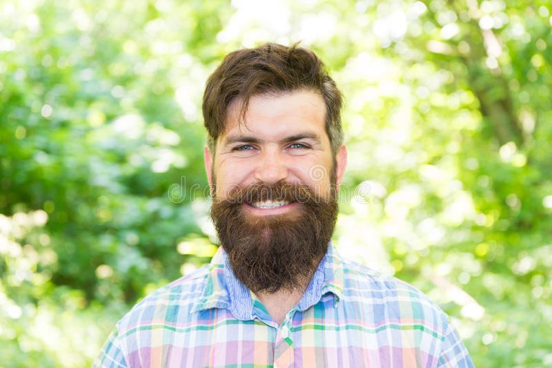 Perfect smile of a confident man. Happy man on natural landscape. Bearded man smiling in casual style on summer day. Caucasian man wearing long mustache and royalty free stock photo