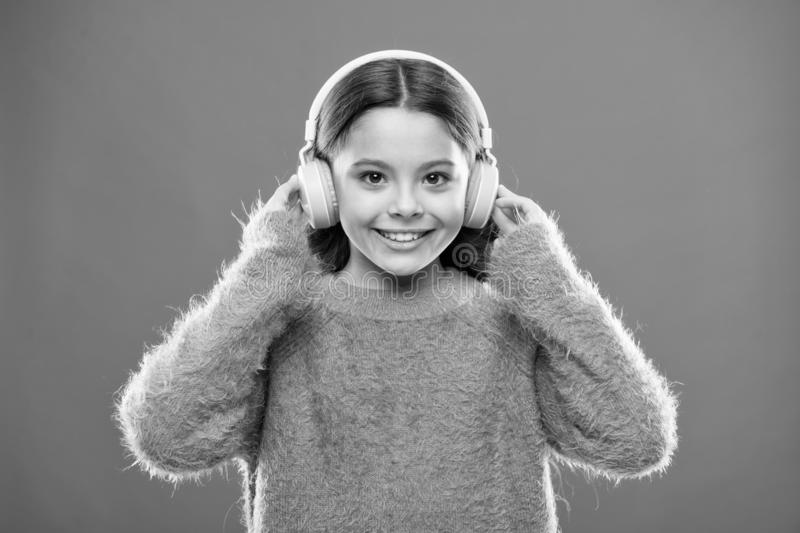 Perfect sound stereo headphones. Girl cute little child wear headphones listen music. Kid listen music orange background royalty free stock image