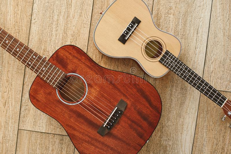 Perfect sound. Top view of the acoustic and ukulele guitars lying close to each other on the wooden floor. Music concept. Musical instruments royalty free stock images