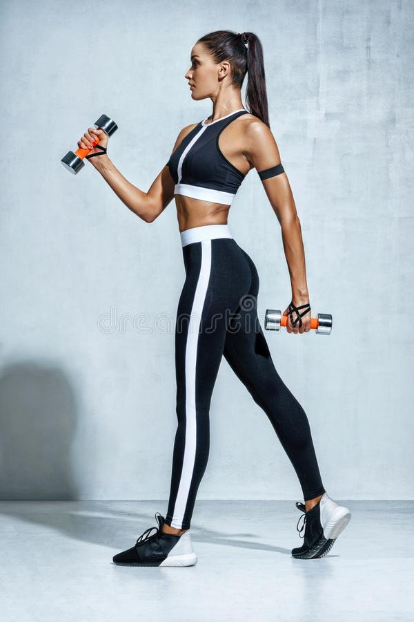 Perfect sporty woman working out with dumbbells. stock photos