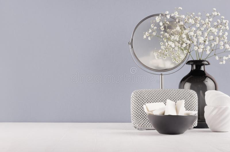 Perfect stylish decoration for home - black glass vase with small flowers, mirror, female silver cosmetic, bowl sponges. Perfect stylish decoration for home in royalty free stock images