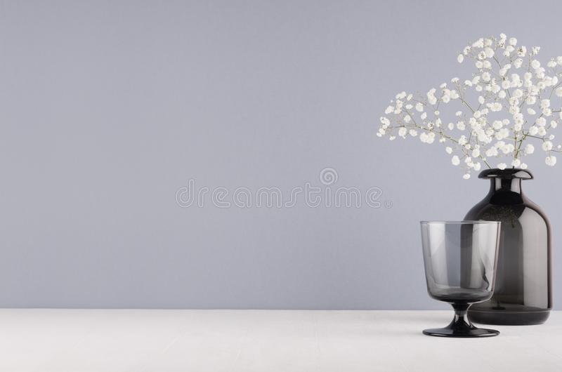 Perfect stylish home festive decoration in grey colors - black glass goblet and vase with small fluffy flowers on soft light white. Wood table stock image
