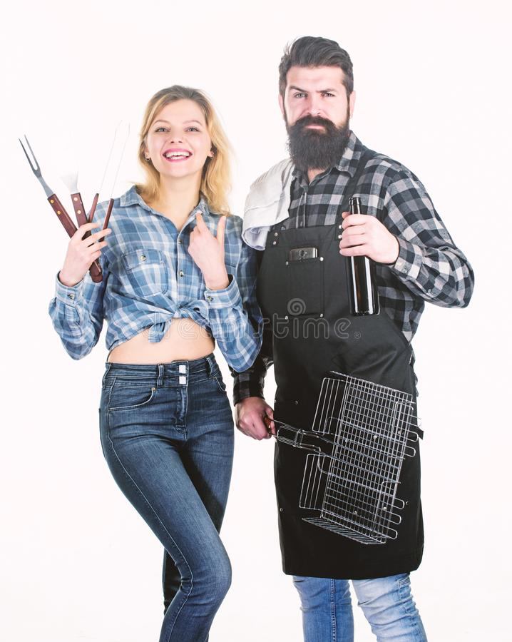 Perfect for a summer cookout. Couple of bearded man and pretty woman holding BBQ set. BBQ is a cooking method. Happy royalty free stock image