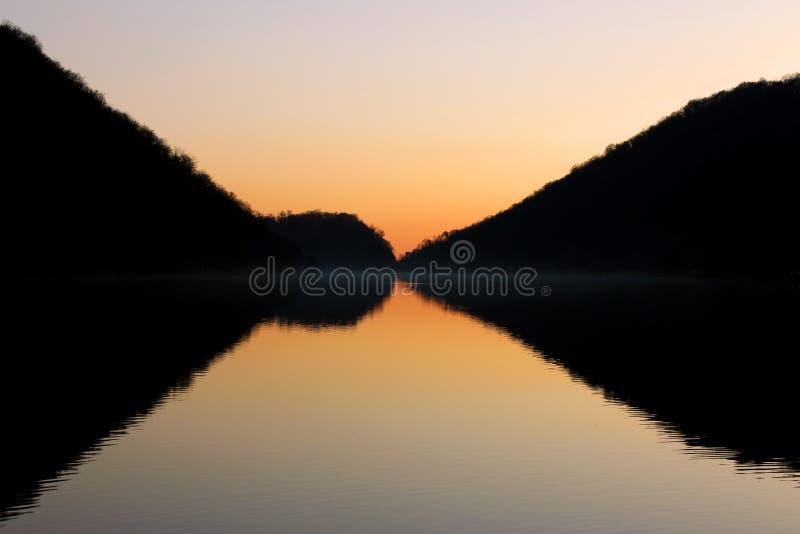 Perfect symetryczny odbicie halna sylwetka na płaskiej jezioro powierzchni zdjęcie stock