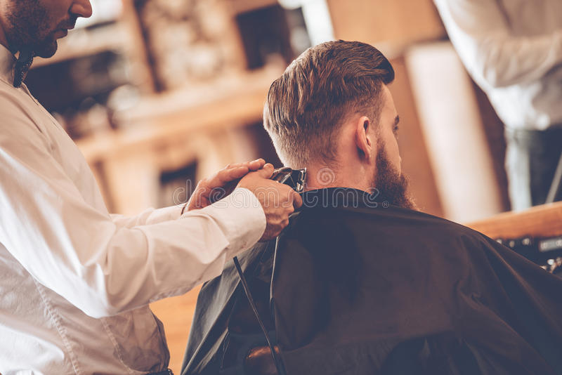 Perfect trim. Rear view close-up of young bearded men getting haircut by hairdresser with electric razor while sitting in chair at barbershop royalty free stock photo