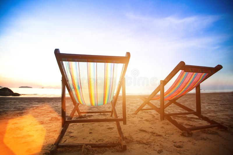 Perfect vacation concept, pair of beach loungers on the deserted coast sea at sunrise. Travel. stock photo