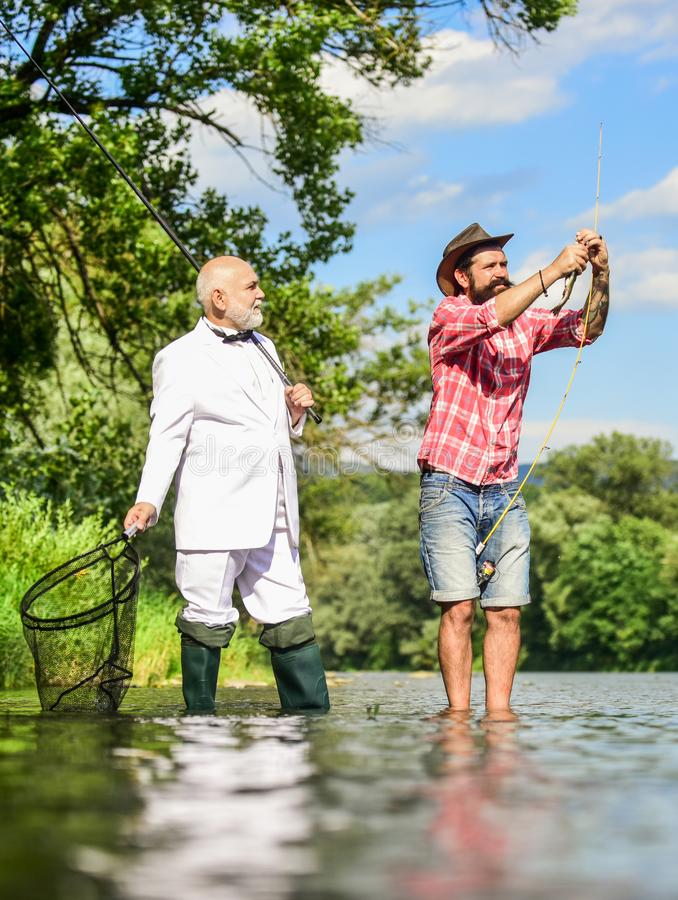 Perfect weekend. Successful catch. Elegant bearded man and brutal hipster fishing. Hobby and recreation. Family day royalty free stock photo