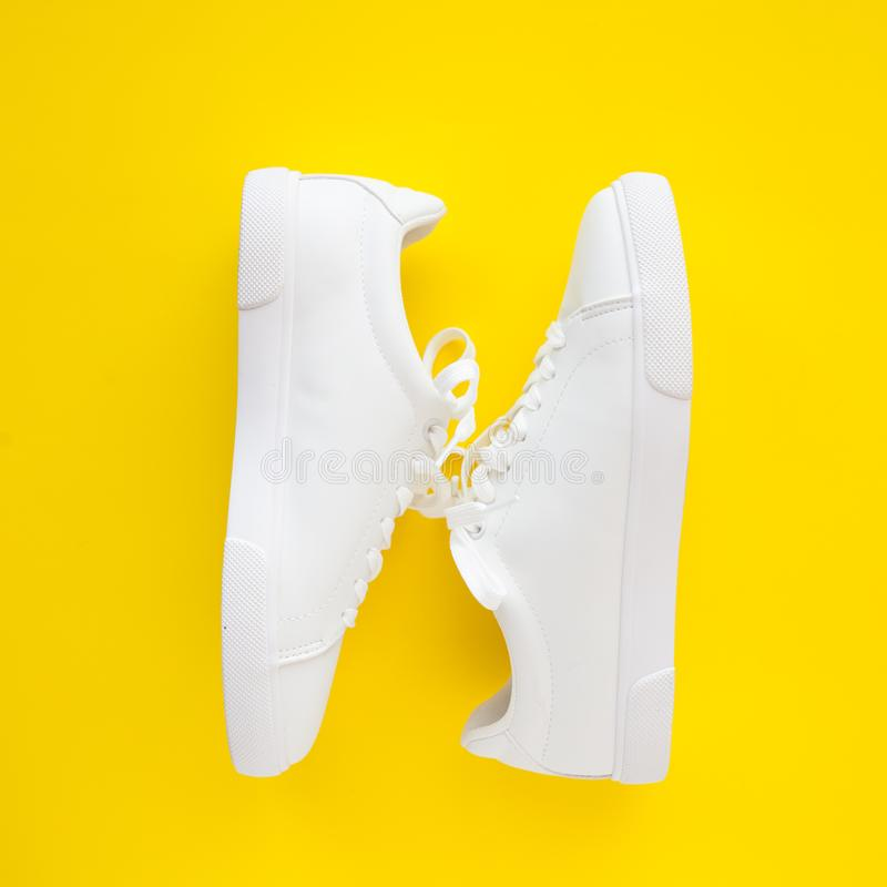 Perfect white New sneakers lie toe to heel on a bright yellow background. royalty free stock photography