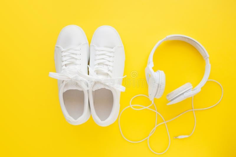 Perfect white new sneakers standing on a bright yellow background near to white headphones. stock photo