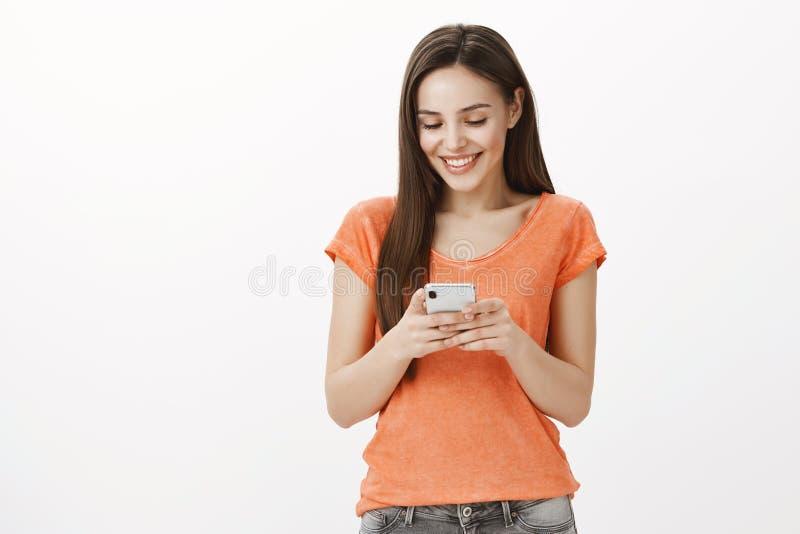 Perfect wiadomość od chłopaka Studio strzelał zadowolona piękna ciemnowłosa caucasian kobieta w pomarańczowym stroju, trzymający fotografia stock