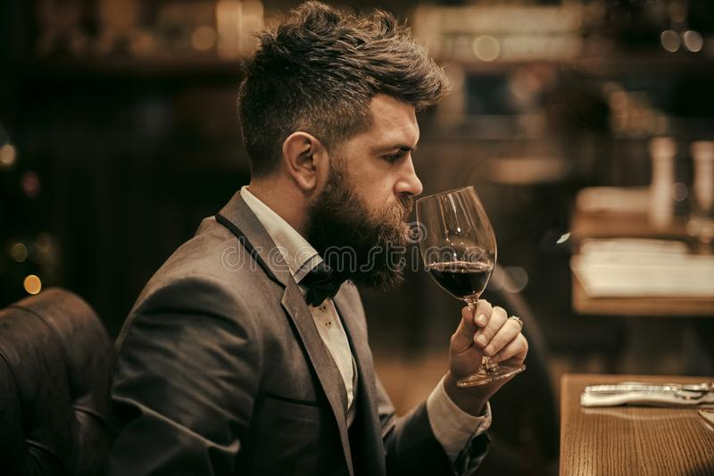 Perfect wine. Businessman with long beard drink in cigar club. bar customer sit in cafe drinking alcohol. Bearded man stock image