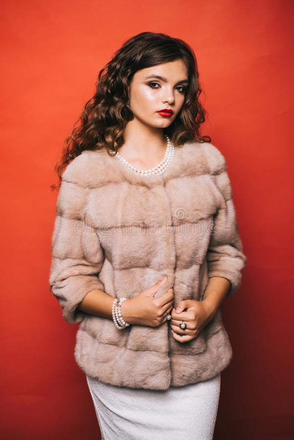 Perfect for winter cold. Young woman in elegant winter coat. Pretty woman in fashionable fur coat. Fashion model wear stock photography