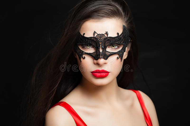 Perfect woman in carnival mask on black background with abstract night glitter bokeh royalty free stock photography