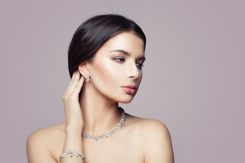 Perfect woman with makeup and diamond necklace, bracelet and earrings on pink background.  stock photos