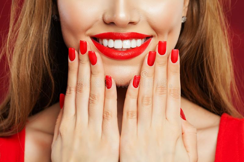Perfect woman touching her face her hand with manicure. Makeup lips with red lipstick and red nail polish, beauty salon concept stock photo