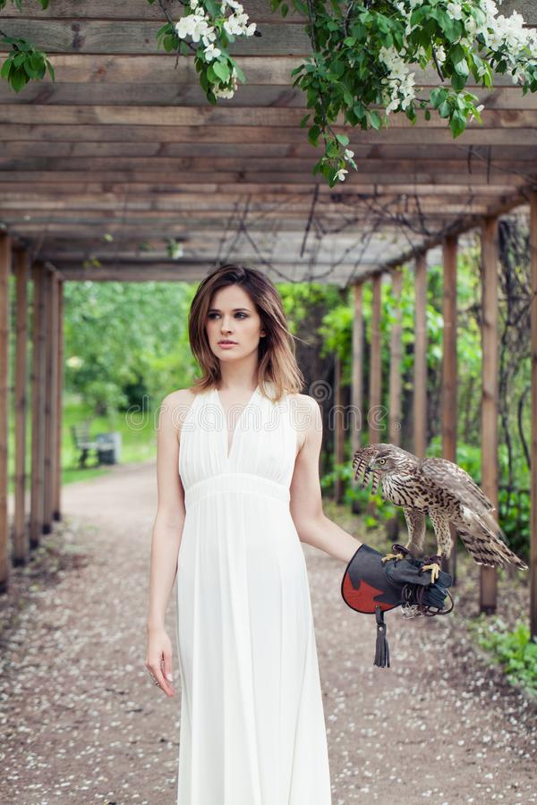 Perfect young woman fashion model in white dress with bird outdoors in park.  royalty free stock images