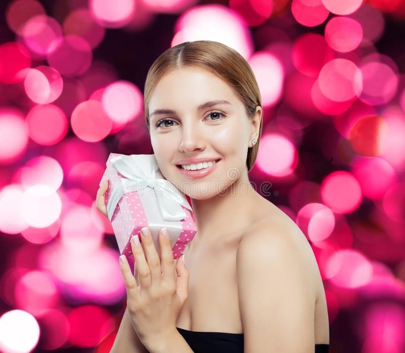 Perfect young woman smiling and holding gift box royalty free stock images
