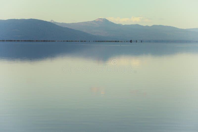 Perfectamente aún aguas en el lago de la montaña foto de archivo