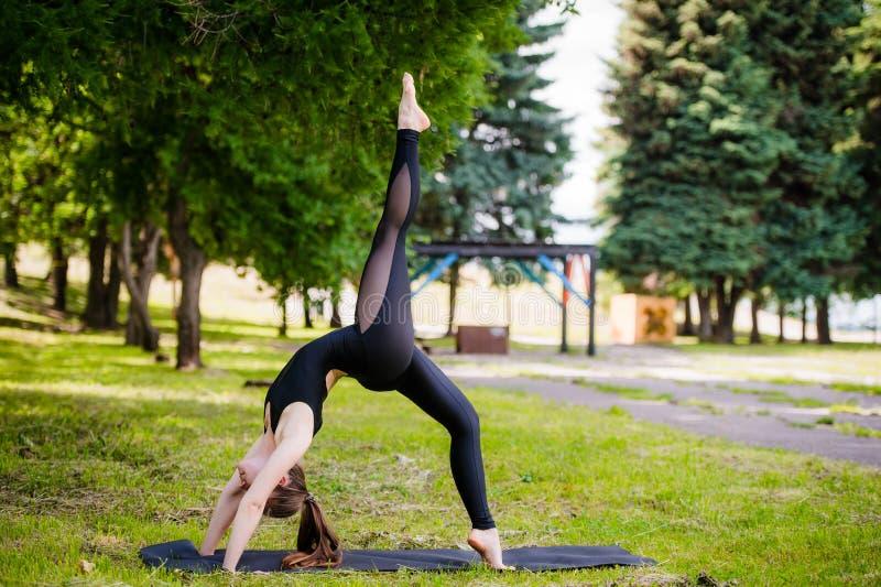 Perfecte acroyoga Het mooie jonge meisje brengt het doen van acro-yoga in evenwicht Openlucht de klassentraining van de yogaflexi royalty-vrije stock fotografie