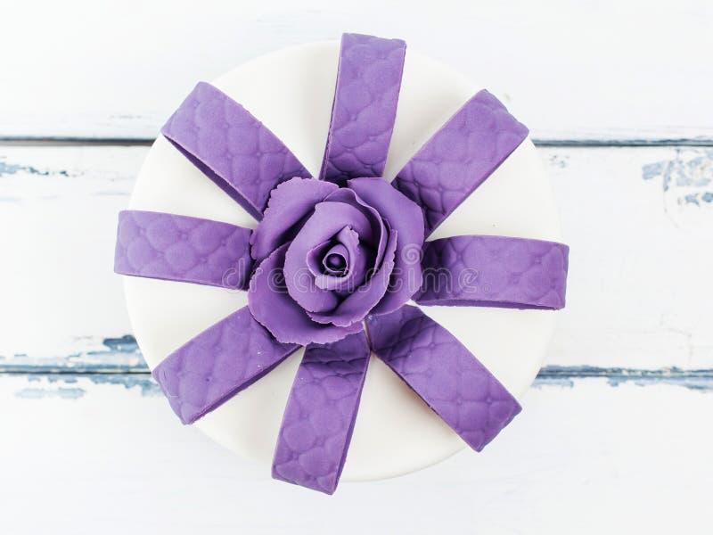 Perfecte cake met lilac roze decoratie op witte houten achtergrond stock foto's