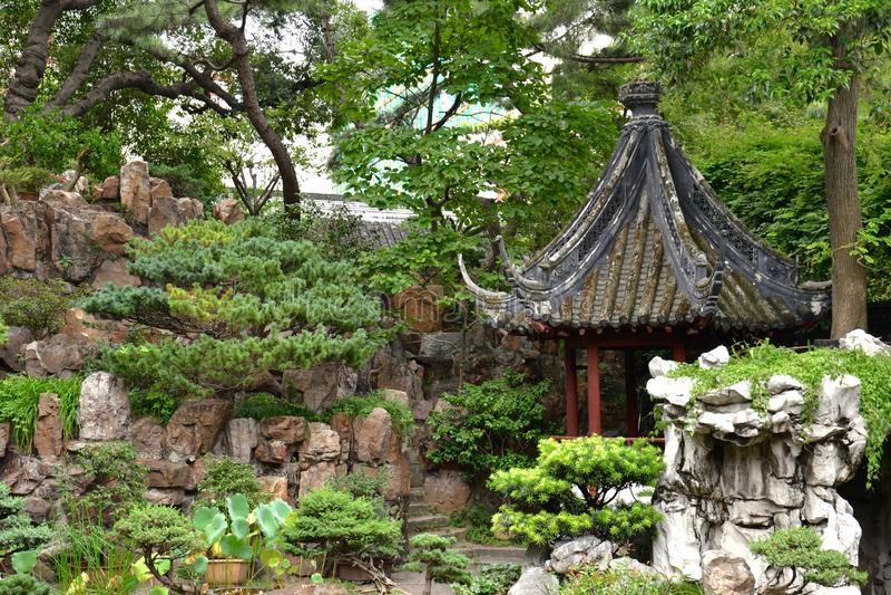 Perfecte Chinese/Aziatische tuin - rockery, groene struiken, pagode en weg stock fotografie