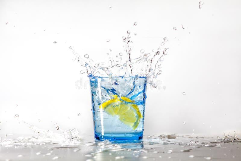 Perfecte citroenplons in een blauw glas water stock foto's