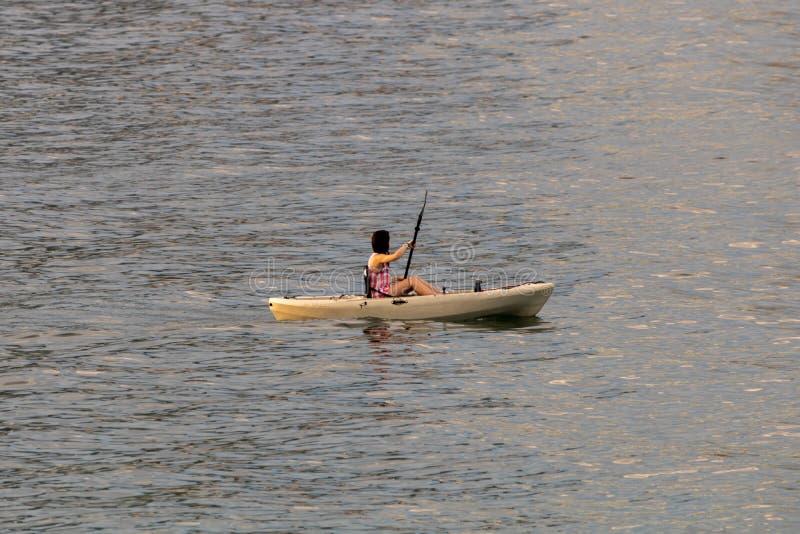 Perfecte dag voor het kayaking Mooie jonge vrouw die terwijl het zitten in kajak paddelen royalty-vrije stock foto's