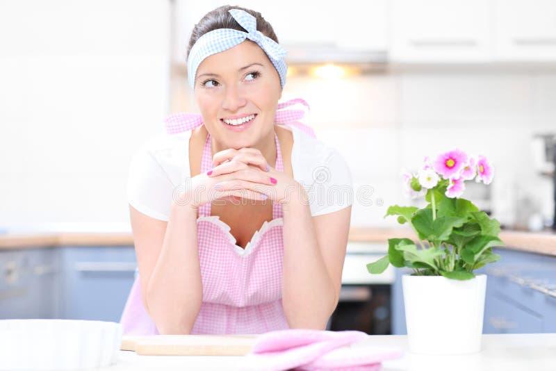 Perfecte huisvrouw in de keuken stock fotografie