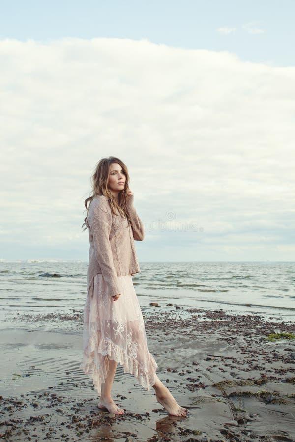 Perfecte jonge vrouw in bohokleding het ontspannen op oceaankust stock afbeelding