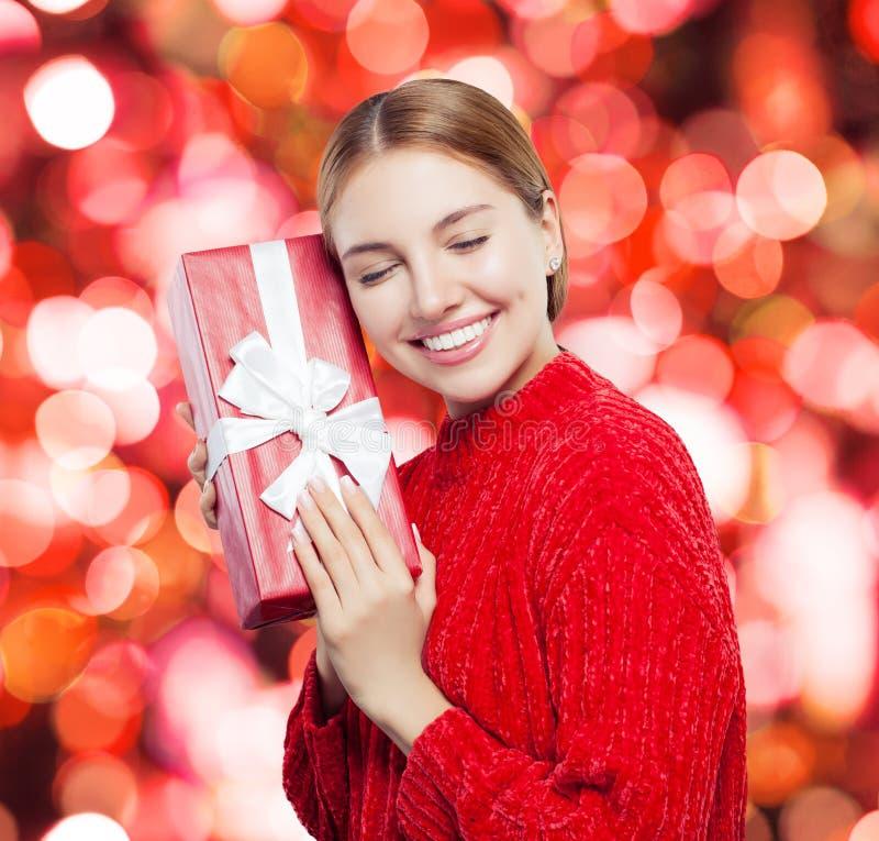 Perfecte jonge vrouw die en rode giftdoos glimlachen houden royalty-vrije stock foto