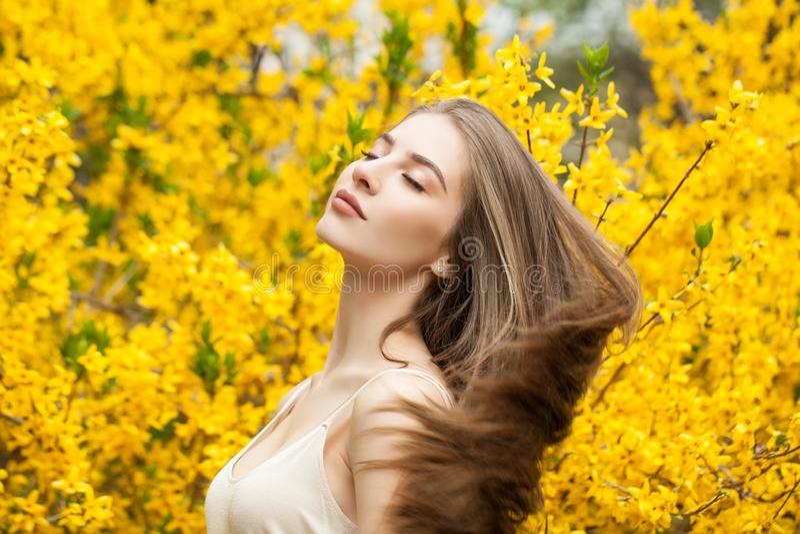 Perfecte jonge vrouw met gezond kapsel op bloemenachtergrond royalty-vrije stock afbeelding