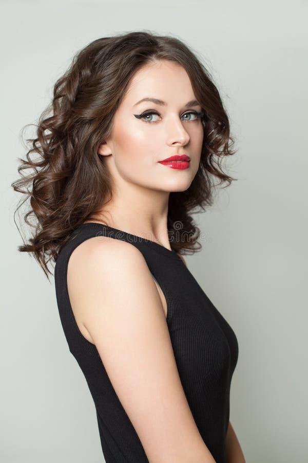 Perfecte jonge vrouw met make-up en bruin krullend haar stock foto's