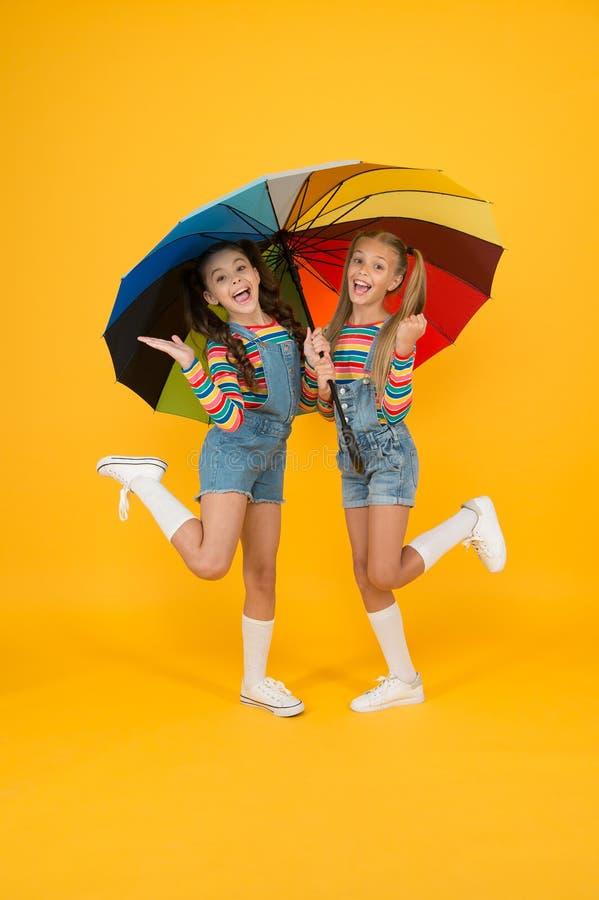 Perfecte verblijfplaats klein meisje onder een kleurrijke paraplu twee gelukkige kinderen gele achtergrond kinderen genieten van  stock fotografie