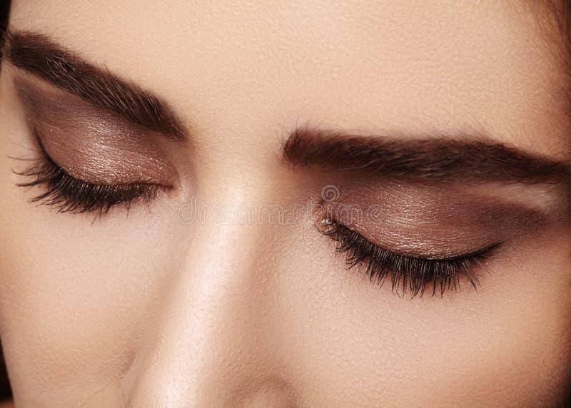 Perfecte vorm van wenkbrauwen, bruine oogschaduw en lange wimpers Close-upmacro van gezicht dat van manier het rokerige ogen word stock foto