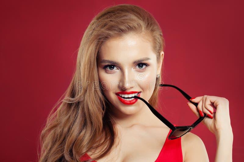 Perfecte vrouw met zonnebril en rode lippenmake-up op kleurrijke rode achtergrond, portret royalty-vrije stock afbeeldingen