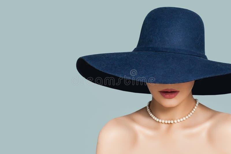 Perfecte vrouw in modieuze hoed en de witte halsband van parelsjuwelen op blauwe achtergrond stock foto