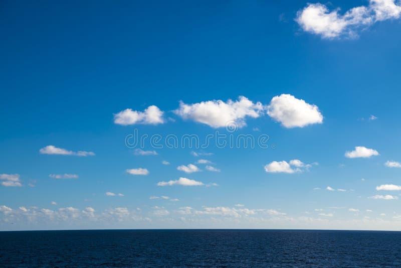Perfecte wolken in blauwe hemel, enige pluizige wolk in heldere hemel over oceaan stock afbeelding