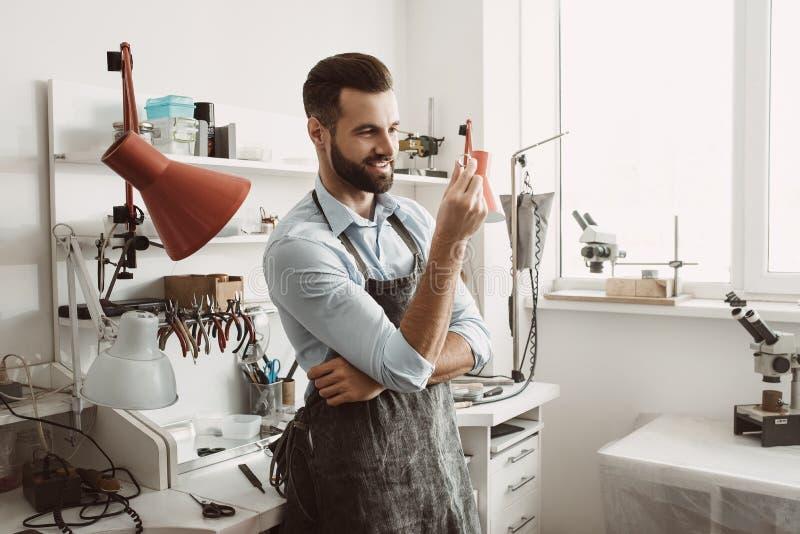 perfectie Portret van jonge en het glimlachen mannelijke juwelier die en een ring inspecteren terwijl status in workshop eruit zi royalty-vrije stock afbeeldingen