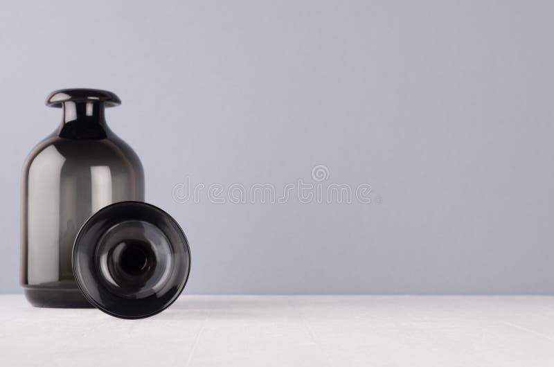 Perfectionnez la décoration à la maison élégante dans des couleurs grises - vase et sphère en verre noirs sur la table en bois bl image libre de droits